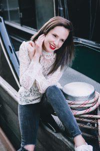 Attraktive braunhaarige Influencer sitzt am Bootssteg und lächelt in die Kamera