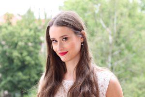 Influencer: Braunhaarige junge, attraktive Frau steht in der Natur. Nahaufnahme