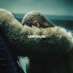 Sängerin Beyonce mit geflochtenen Haaren. Sie verdeckt ihr gesicht mit ihren Armen, steht seitlich zur Kamera und hat einen fkauschigen Mantel an