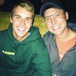 Justin Bieber mit Freund. Sie lächeln beide in die Kamera. Der Freund trägft Brille und Cap