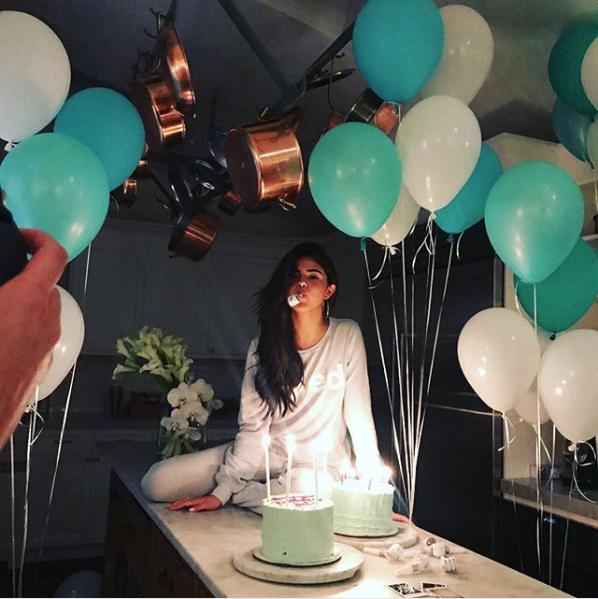 Selena Gomez in einer Küche. Viele Luftballons schweben an der Decke, zwei Torten stehen auf dem Küchentisch. Selena Gomez sitzt dahinter und hat eine Geburtstagströte im Mund