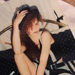 junges Mädchen mit Hut auf dem Bett. Lockige Haare.